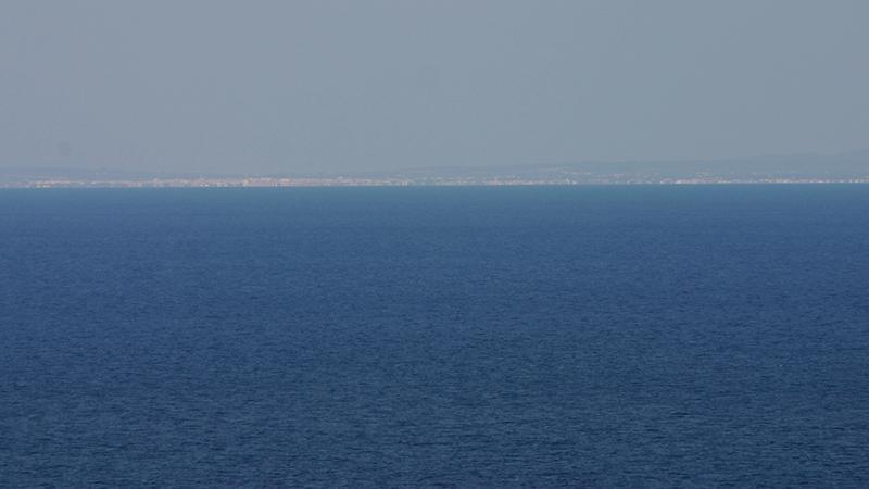 Hinterm Horizont, im Dunst, erhebt sich Menorca
