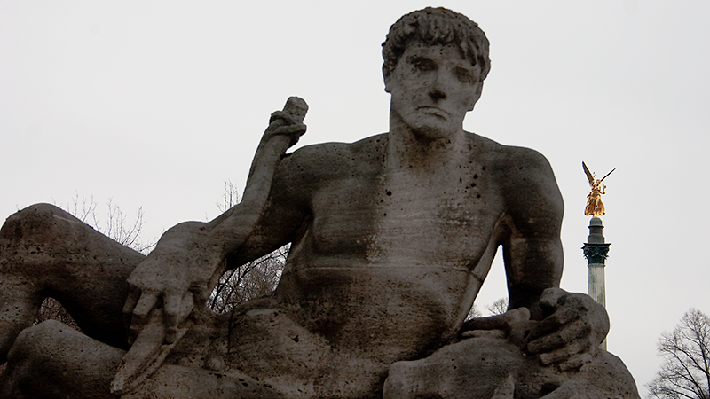 """Steinfigur """"Baiern"""" mit Friedensengel im Hintergrund"""