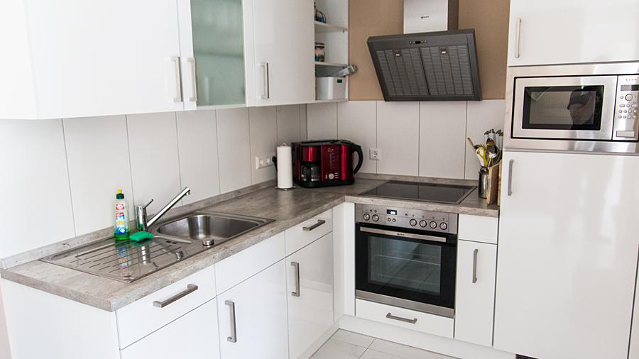 Küchenbereich mit Spülmaschine, Cerankochfeld, Backofen, Mikrowelle und Kühlschrank mit Gefriermöglichkeit