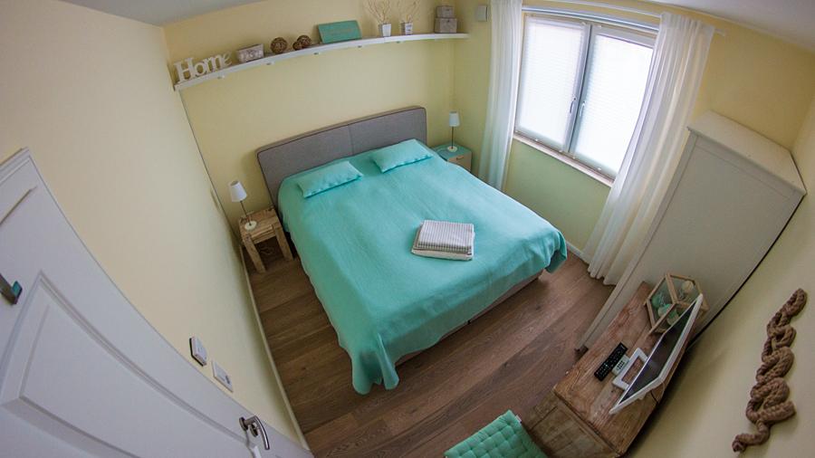 Blick ins Schlafzimmer: klein, aber zweckmäßig und gemütliches Lichtkonzept